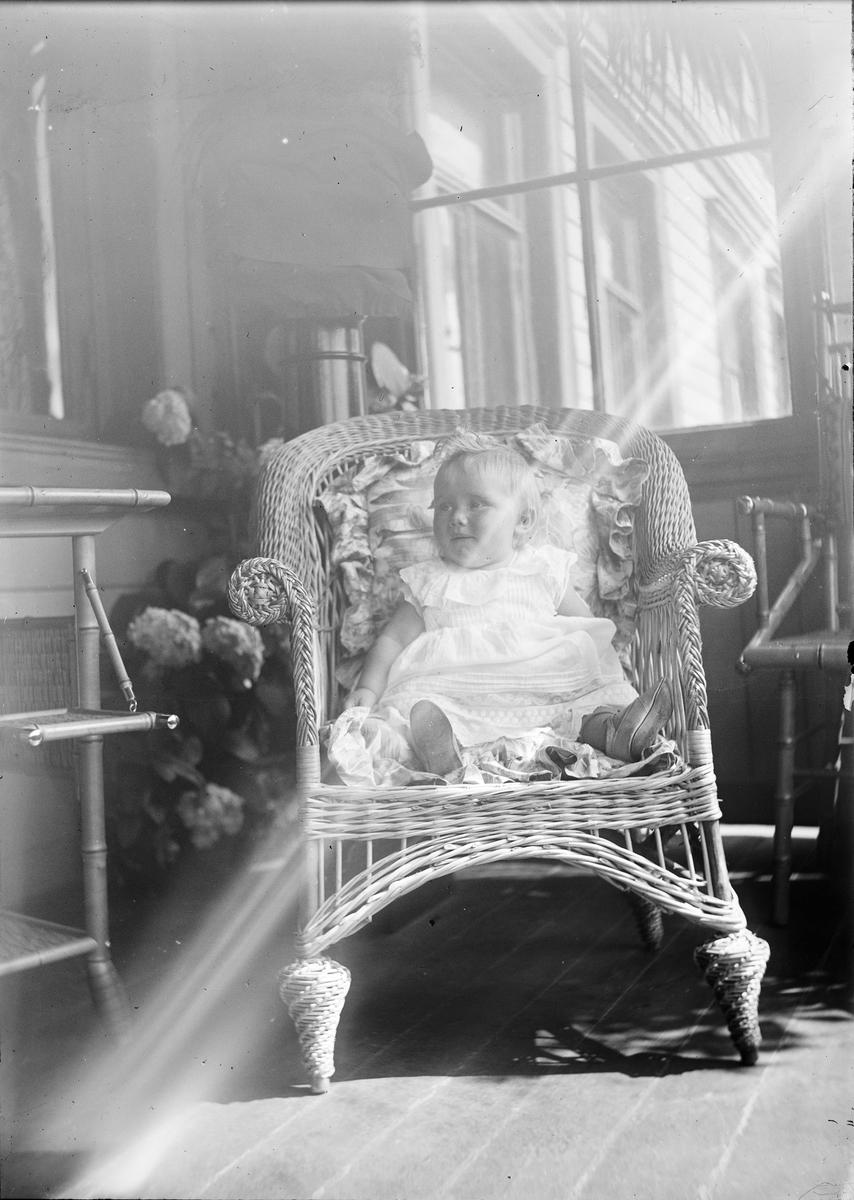Et barn sitter i en kurvstol på en veranda hvor solen lyser opp motivet. I bakgrunnen sees vinduer inn til huset og blomstrende hortensiaer.