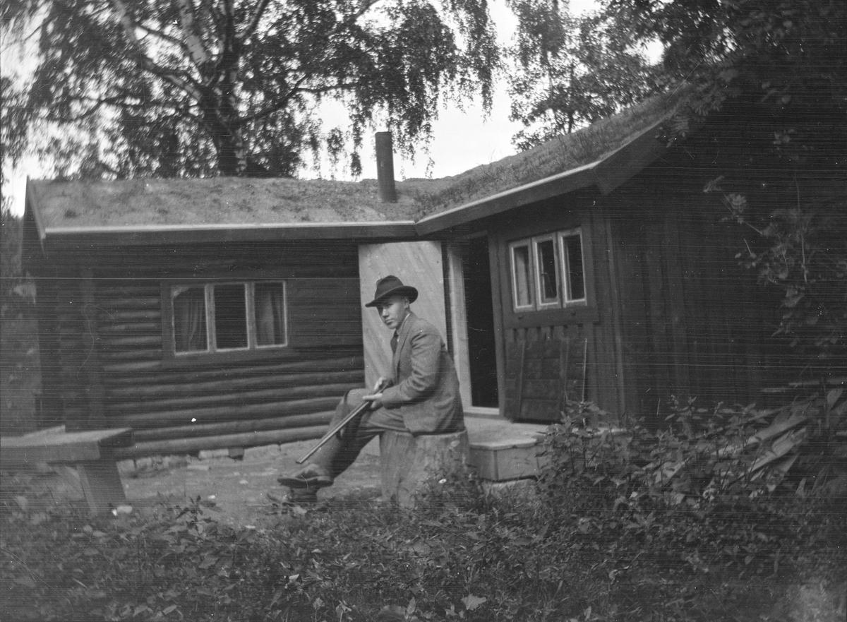 Iacob Ihlen Mathiesen sitter på en stor stubbe utenfor en tømmerhytte med torvtak. På fanget har han et jaktgevær Bildet er tatt sensommer eller høst.