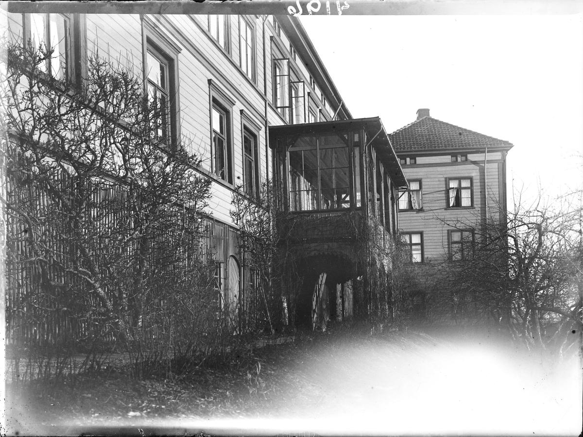Dette er et bilde av hovedhusets fasade, den som vender mot terrassehagen. En gangsti går langs grunnmuren. Det er plantet klatrevekster og busker langs stien. Noen vinduer i annen etasje står åpne.