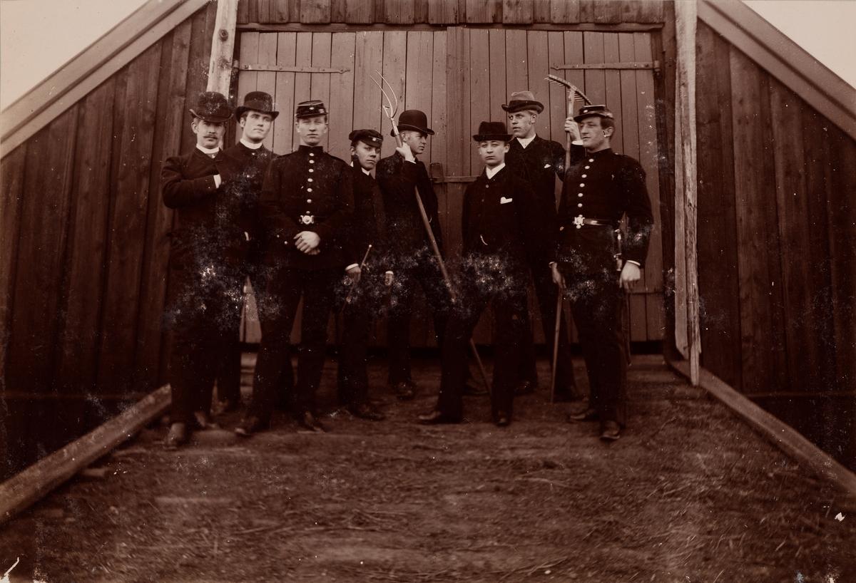 Åtte unge menn poserer på låvebrua på Linderud Gård. Fra venstre: 4. Christian Pierre Mathiesen med studenterlue, 6. Johan Wetlesen, 7. Herman Anker.