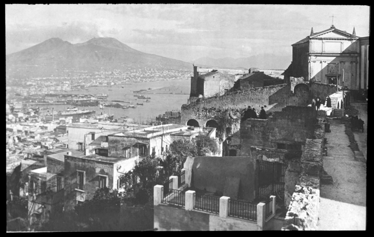 Skioptikonbild från institutionen för fotografi vid Kungliga Tekniska Högskolan. Motiv föreställande Neapelbukten med Vesuviuas i bakgrunden,  Italien. Bilden är troligen tagen av John Hertzberg under en resa i Europa..