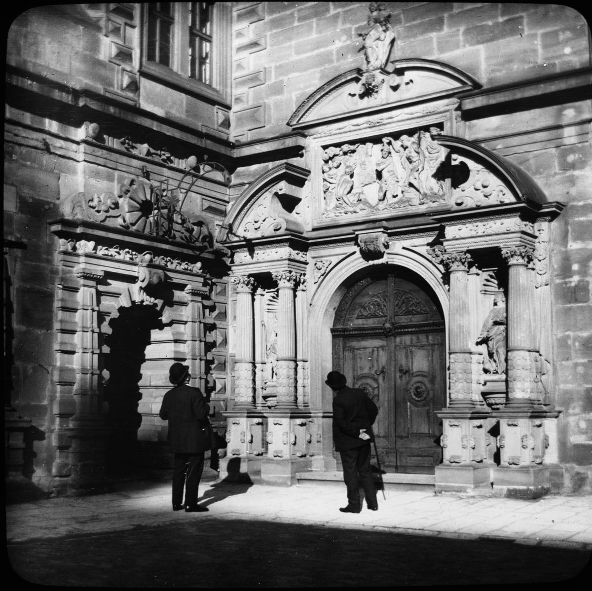 Skioptikonbild med motiv av två män vid porten till slottet Johannisburg i Aschaffenburg. Bilden har förvarats i kartong märkt: Resan 1908. Aschaffenburg 7. XXVIII.