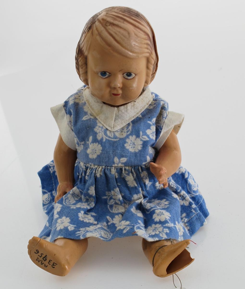Dukke av støpte plastdeler. Hode og kropp i ett, mens armer og ben er støpt for seg og montert med strikk. Hjemmesydde klær: (?)  Blå blomstret kjole. Undertøy.