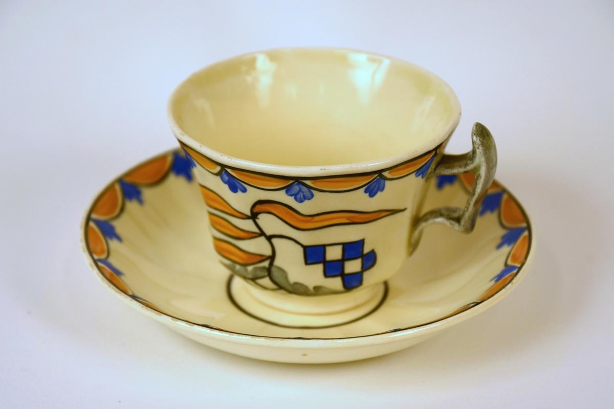 11 kopper med skål til servise i off-white glasur. Dekor RAKLER: kantet  i gultt/blått/sort mønster. Midtstilt dekor i tilsvarende farger og grått.