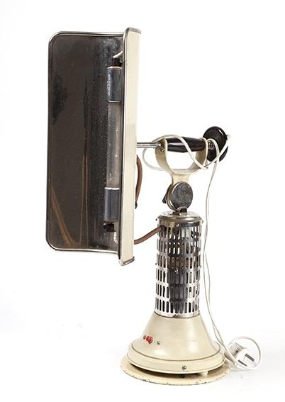 """Solariumslampe for hjemmebruk- """"høyfjellsol"""". Rund fot, lang, smal skjerm rundt lysrør. Antatt produsert i 1930-årene, tysk prod. Lakkert, forkrommet. Nettkabel."""