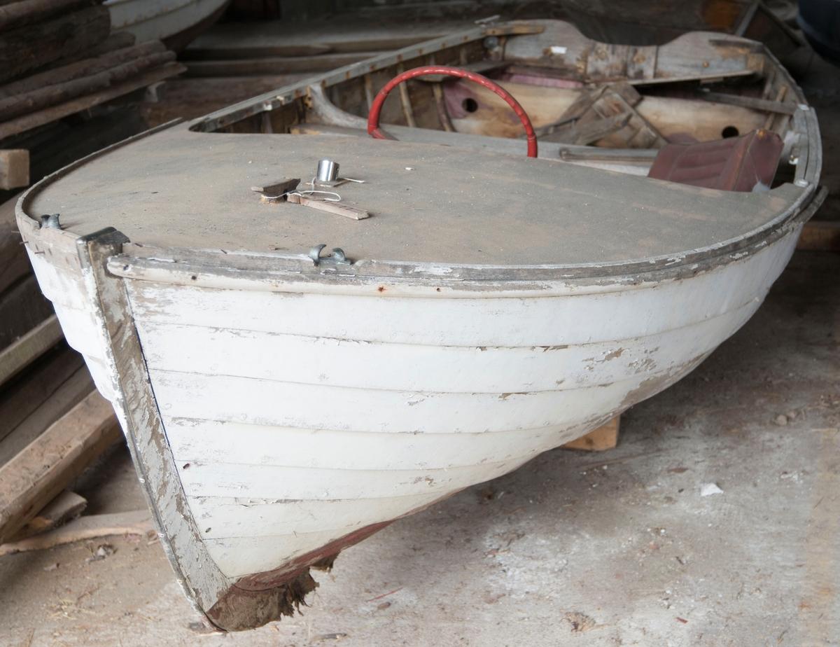 Hvit passbåt, halvdekk foran. Klinkbygd med ribber - mahogny på eik. 8 bordganger.