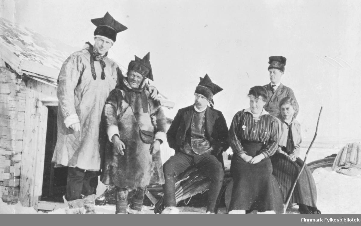 Sjursjavre, mars 1917. Gruppebilde av nordmenn og same i pesk. Nordmenn med samiske luer på hodet.