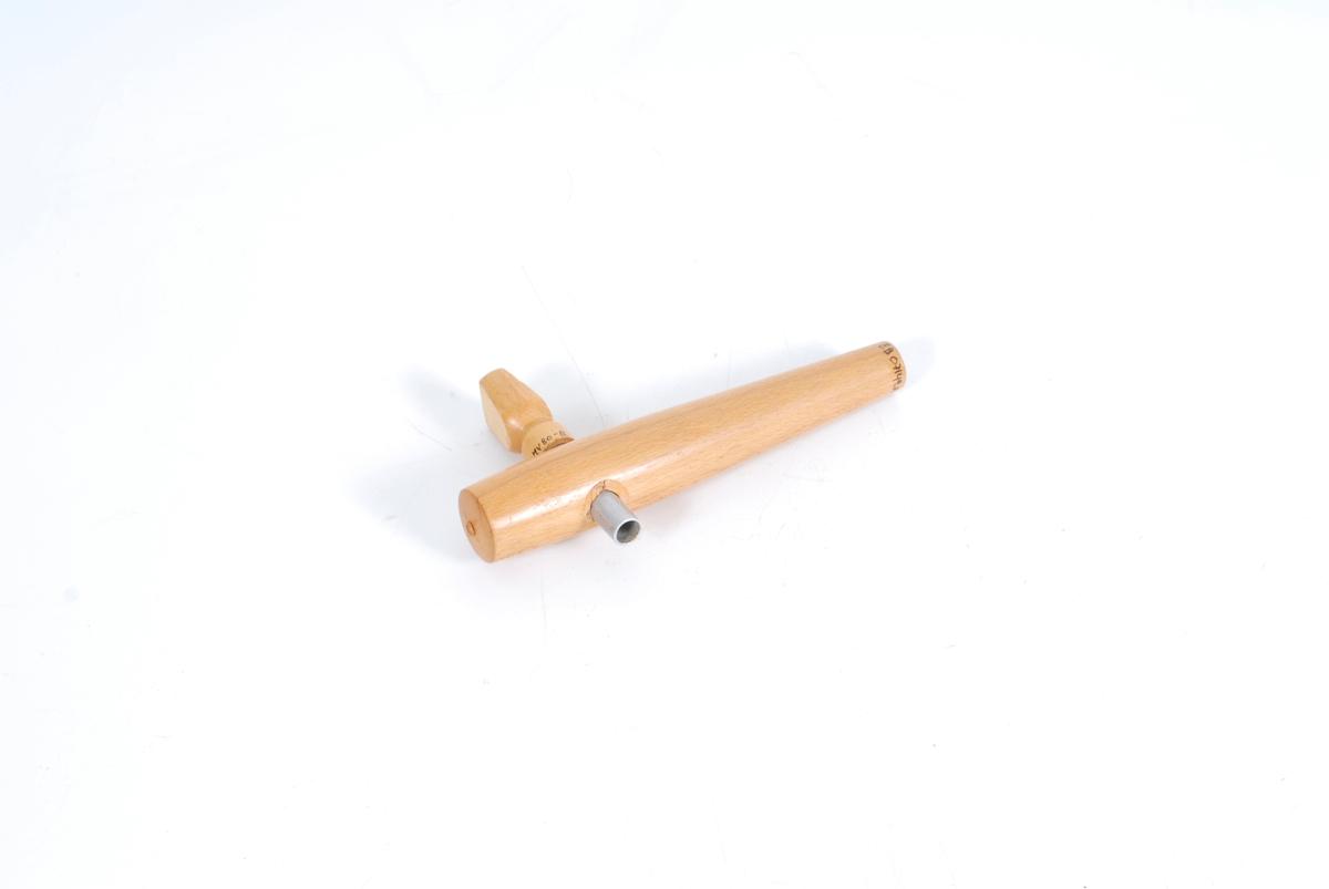 treplugg til å sette i spunshull. Metallrør går tvers gjennom trepluggen. Dette utgjør en tappekran. 2 deler: a) treplugg med hull b) metallrør med hull og trehåndtak