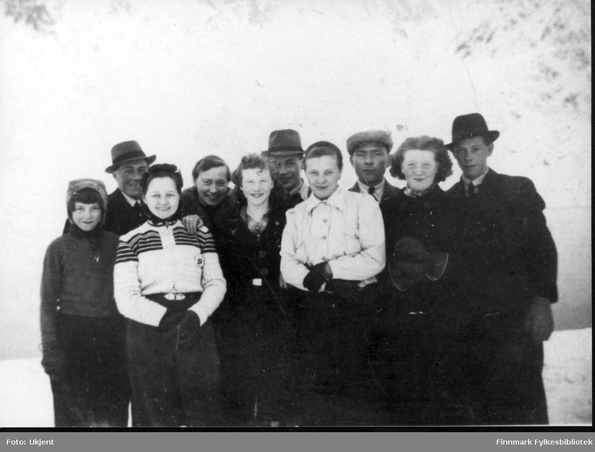 En gjeng ungdommer fra Nuvsvåg, bildet tatt omtrent 1941-42. Fra venstre: Amanda Berutzen, Otto Olsen, Agnes Flatmo, Dagmar Nutu, Margot Berutzen, Håkon Andersen, Olga Olsen, Lars Karlsen, Cesilie Nilsen og Berut Berutzen. Bildet er utlånt av Terje Johnsen. Pikene er kledd i jakker, gensere, hansker og luer. Guttene har på seg hatter og jakker.