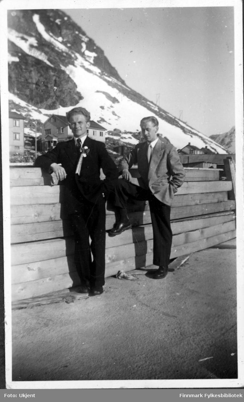 Magnus og Asbjørn Martinsen feirer 17.mai i Øksfjord en gang på 1960-tallet. De to brødrene er kledd i fest klær: dress med slips. De lener seg mot et tregelender og i bakgrunnen kan man se hus og fjell.