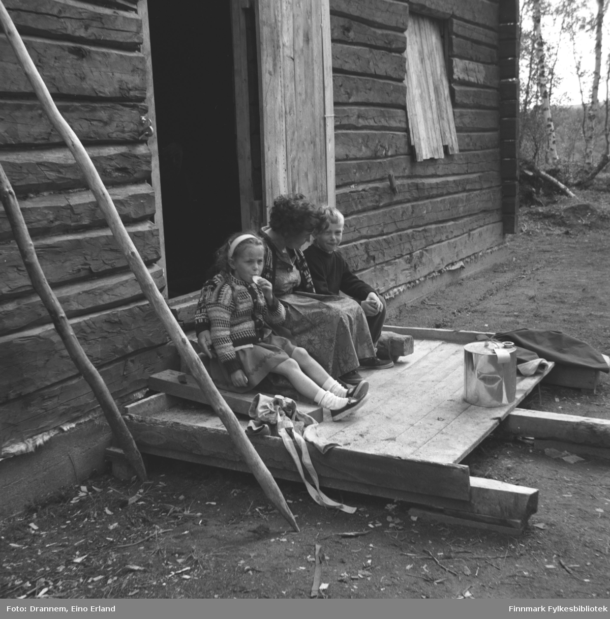 Tre personer sitter på et platting foran en hytte. De er fra venstre: Kari Gabrielsen, Sonja Lappalainen og Ole Gabrielsen.