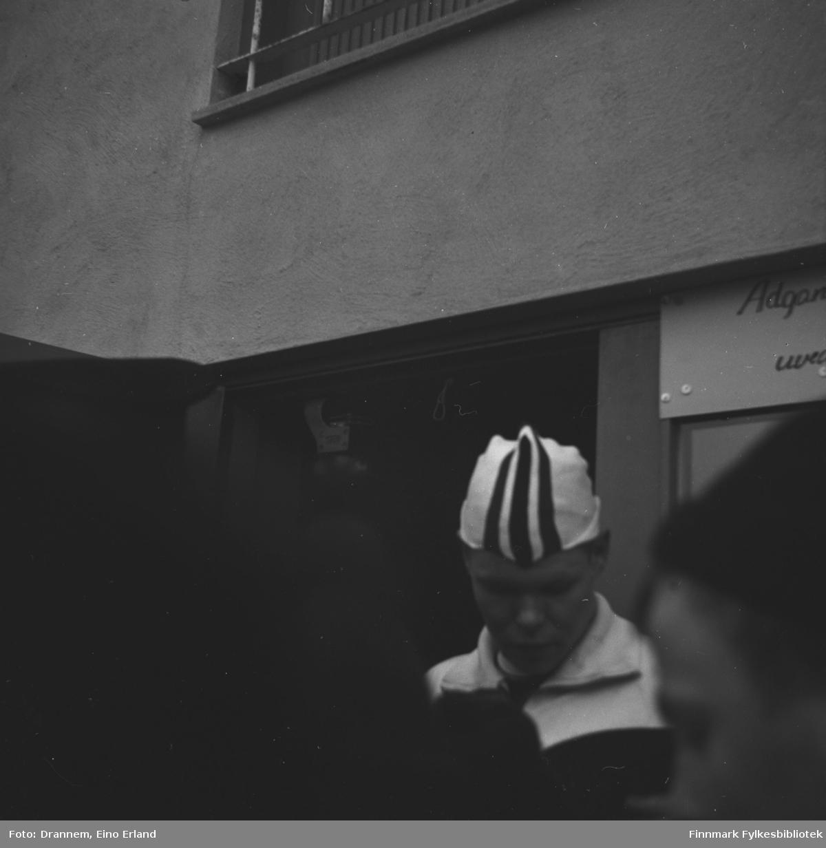 Skøyteløperen Per Ivar Moe står inntil en vegg med endel mennesker foran seg.
