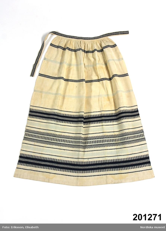 Förkläde av  vitt tuskaftat bomullstyg med invävda tvärrbårder i rosengång med mörkblått, ljusblått och vitt bomullsgarn. Rynkat mot 2 cm linning med mönsterbård i mörkblått med knytning i vänster sida.  I sidorna stadkant, nedtill  2 cm bred fåll. Handsytt.  dessa tvärmönstrade förkläden blev moderna under 1890-talets nationalromantiska  period när de gamla traditionella vävteknikerna kom på modet.  Har tillhört Augusta Dolk i Vämboö. Urshult. Anm. Den ljusblå färgen något blekt. /Berit Eldvik 2012-5-14