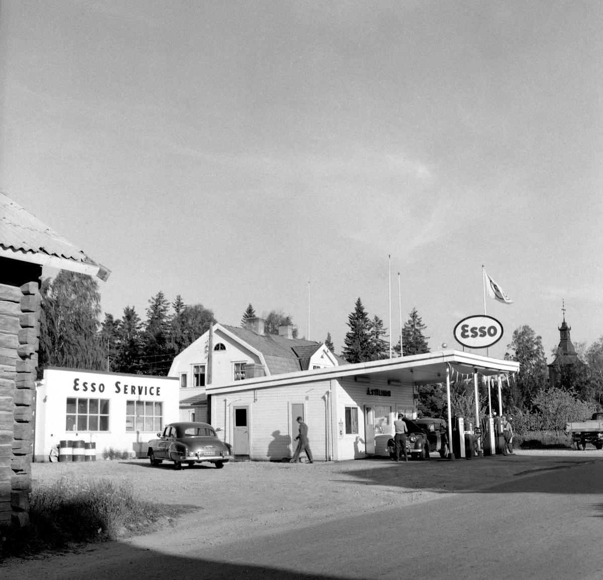 """Någonstans i Värmland - från slutet av 1950-talet. Kommentar från användare: """"Det är Esso i Ekshärad med kyrkan i bakgrunden. Fotot taget från nordväst""""."""