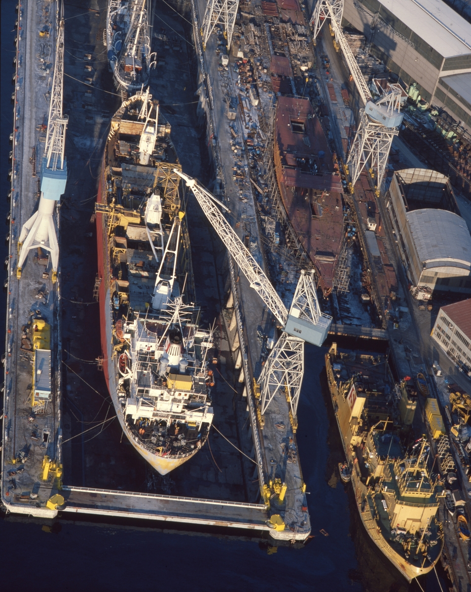 """H.M.V. Flyfoto. Verftområdet. Flere skip ved kai. Seilskipet """"Stadsraad Lehmkuhl"""" i bakgrunnen.  Supplyskipet """"Seaway Falcon"""" til høyre i bildet."""