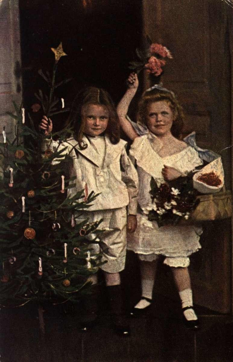 Julekort. Jule- og nyttårshilsen. Koloret fotografi. To piker ved et pynte juletreet. Stemplet 24.12.1918.