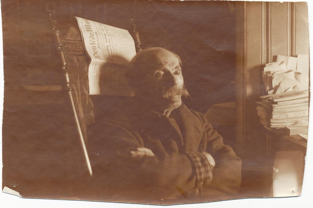 """Arne Garborg sitter på en stol med et eksemplar av """"Den 17.de Mai"""" hengende på stolryggen."""