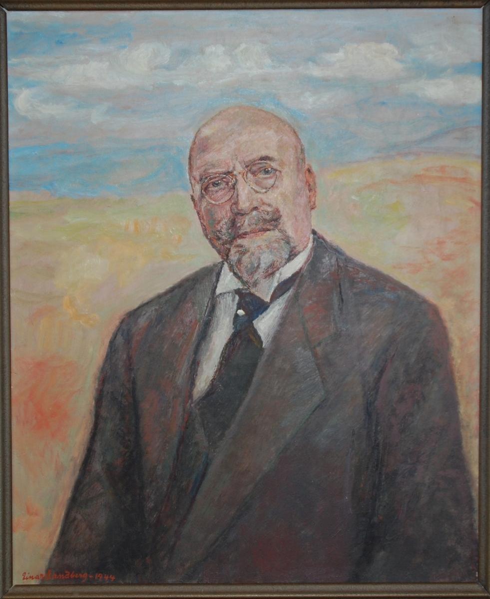 Maleri i ramme. Portrett av Anders Sandvig, brystbilde en face, kroppen litt dreid. Han er iført dress og slips med slipsnål på knuten, og har lorgnett på nesen. Enkelt landskap og skyer i bakgrunnen. Malt med oljemaling på huntonittplate. Rammen er en rikt profilert trelist med bronsemaling.