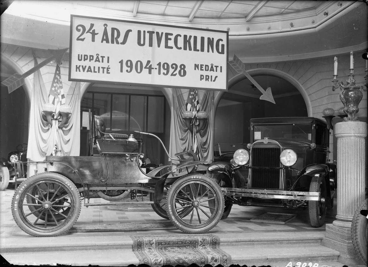 """Bilar på utställning i Ostermans marmorhallar. Skylt: """"24 års utveckling. Uppåt i kvalité 1904-1928 nedåt i pris."""". Bland annnat Oldsmobile."""