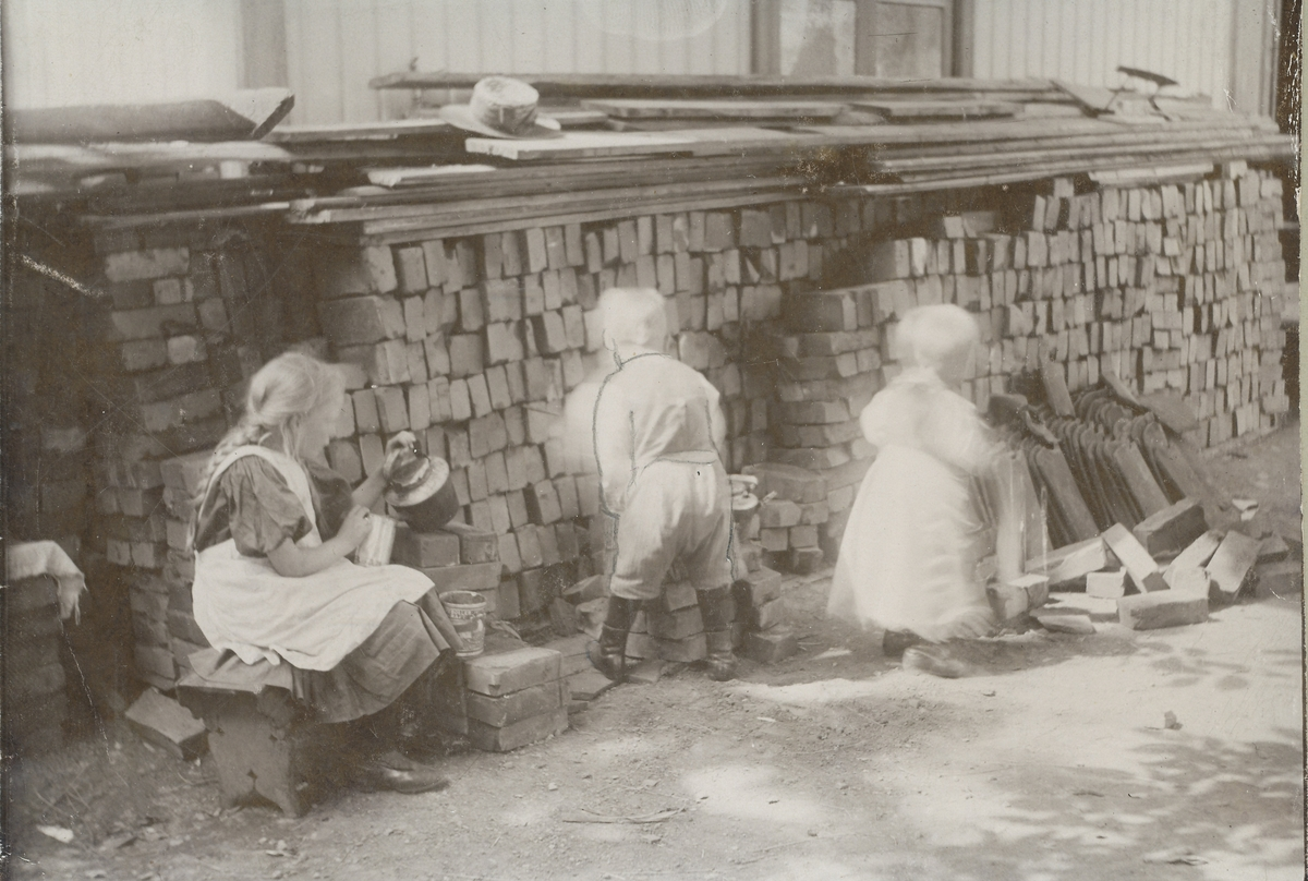 Tre små barn leker ved et mursteinslager.