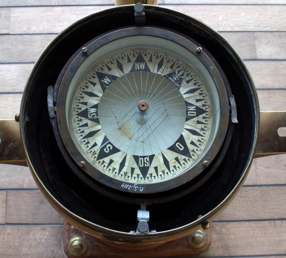 Luftkompass opphengt i slingrebøyle. Bollen er laget av metall og har dobbel bunn fylt med olje for å balansere bollen. Montert i natthus BSJ.03468.