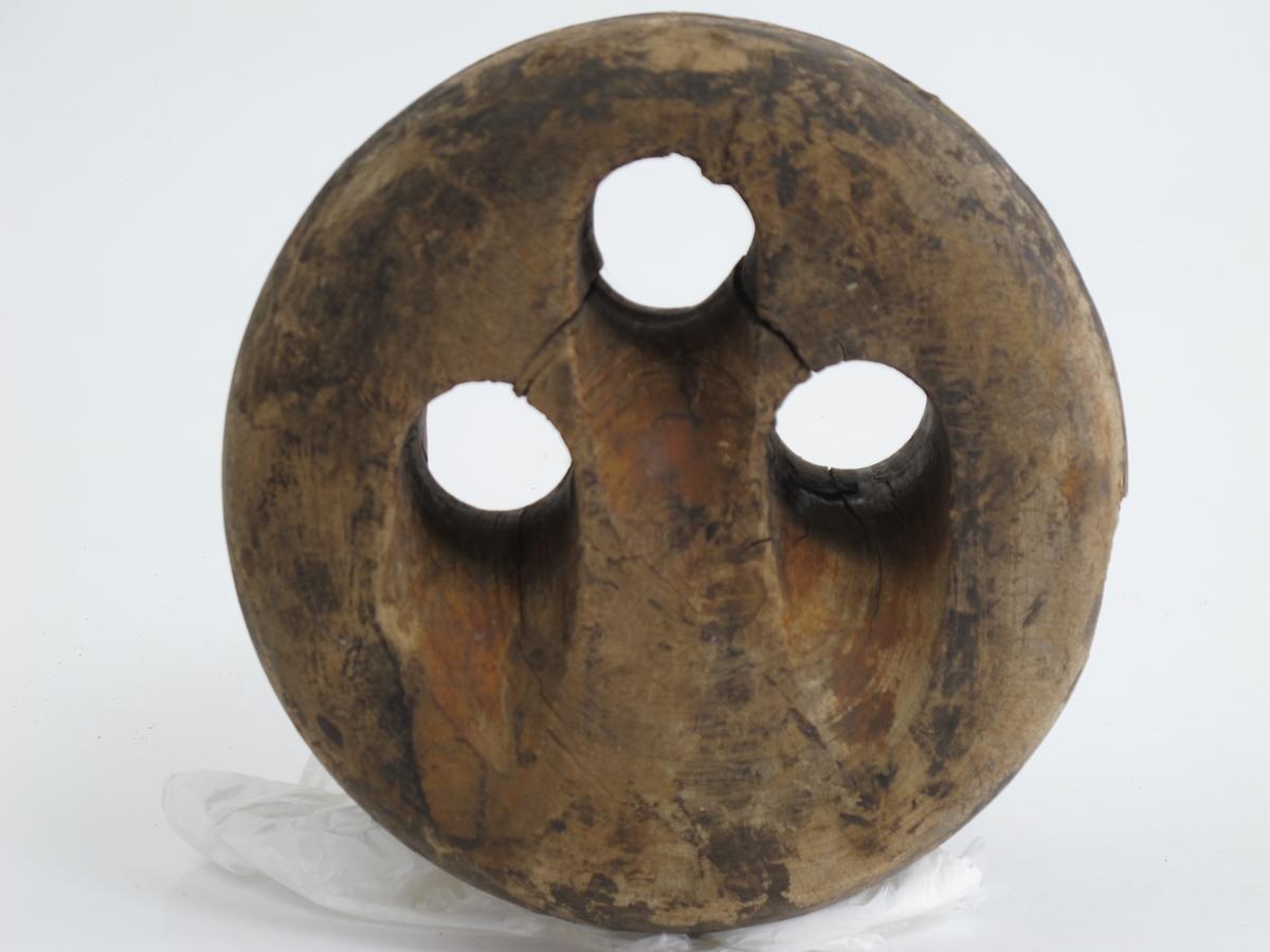 Jomfru, dreid av et stykke tre, trolig ask eller lønn.  3 ovale gjennomgående hull. Spor rundt sidene. 2 like store jomfruer.