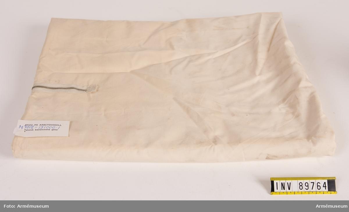 Säck av vit bomullsväv ihopsydd i tre sidor. Mitt på en öppning som går att stänga med blixtlås.