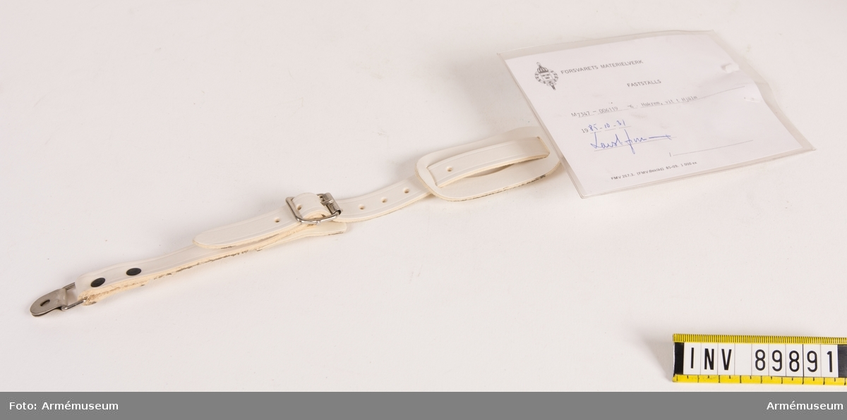 """Hakrem i vitmålat läder med metallspännen  Vidhängande modellapp med text: """"Försvarets materielverk. Fastställs. M 7347-006119-6. Hakrem, vit t Hjälm. 1985-10-31. (oläslig underskrift)."""""""