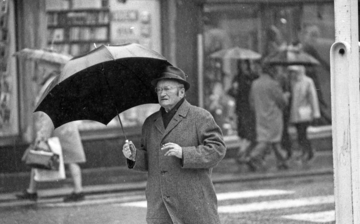 Regnværsbilder. En travel bygate med paraplybærende innbyggere som haster avsted i regnværet.