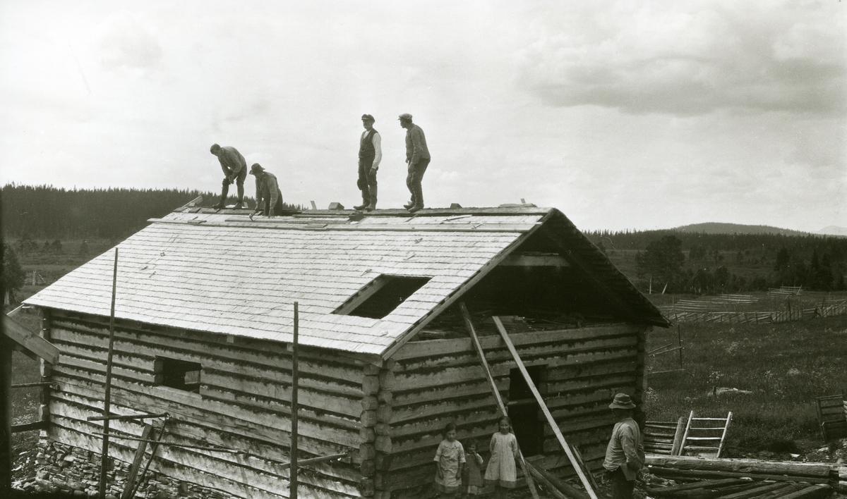 Husbygging i Galåsen. Fire menn i arbeid oppå taket. Tre jenter og en mann står nede på bakken innved veggen. Jentene er sannsynligvis Ingebjørg (1915 - 1999), Elfrid (1919 - 2010) og Maalfrid (1914) Galaasen. Mennene oppå taket (fra venstre): nr. 3, Lars Bjørkli (?) (1868 - 1956), nr. 4, Karl Halaasen (?) (1874 - 1962)