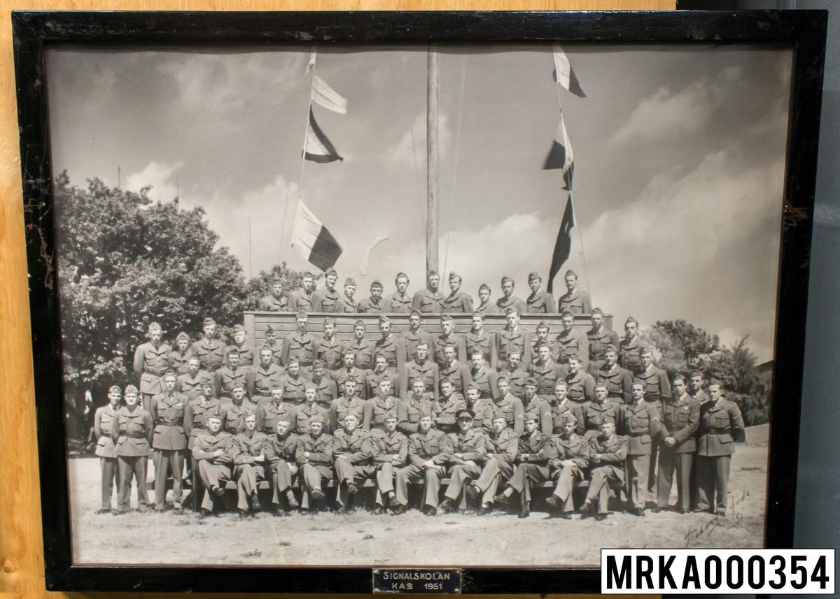 Fotografi taget på befäl och soldater som genomfört grundläggande soldatutbildning på 1:a Batteriet KA 2. Fotografiet taget utanför gymnastiksalen Gräsvik KA 2. Flobergs Foto 1951.