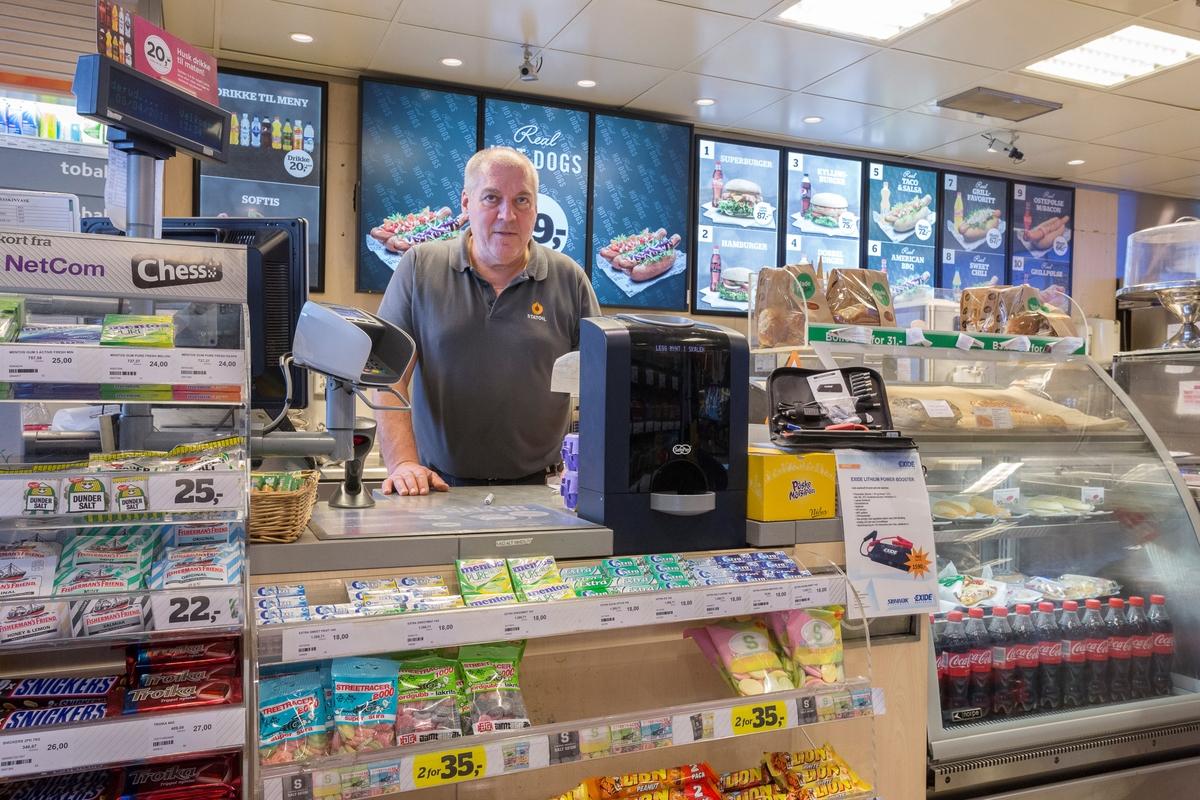 Statoil Nadderud. Butikkbetjening ved butikkdesk. Kortautomat og varer på og rundt disken. Reklame for varm mat i bakgrunnen.