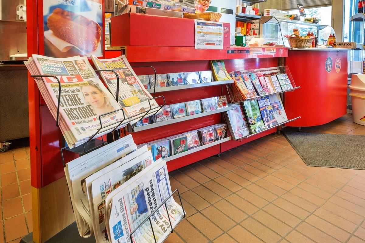 Statoil Hemnes. Butikk interiør med butikkdisk. Foran på disken hyller med musikk-cd`er og et stativ med aviser.
