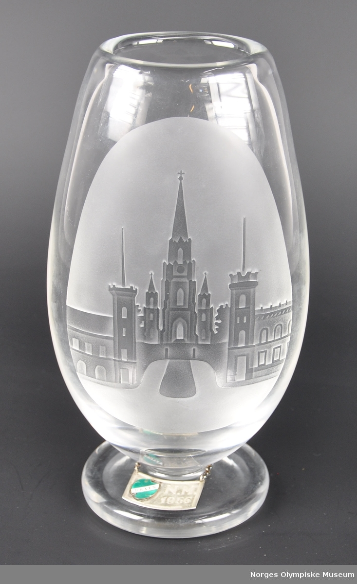 Oval blomstervase av glass med frostet bilde av hus/slott og rund fot. Kjede rundt foten med metallbrikke merket DRAFN N.M. 1956.