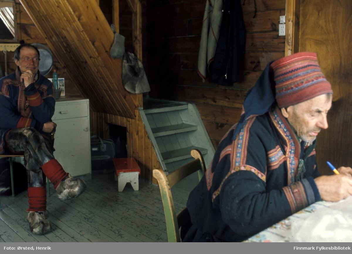 """Postfører Mathis Mathisen Buljo, bedre kjent som """"Post-Mathis"""" i samiske kretser, besøker en av sine postkunder på postruta. Her signerer Mikkol Ailo - eller Aslak Mikkelsen Sara på norsk -  papirer ved kjøkkenbordet.   Fotograf Henrik Ørsteds bilder er tatt langs den 30 mil lange postruta som strakk seg fra Mieronjavre poståpneri til Náhpolsáiva, videre til Bavtajohka, innover til øvre Anárjohka nasjonalpark som grenser til Finland – og ruta dekket nærmere 30 reindriftsenheter. Ørsted fulgte «Post-Mathis», Mathis Mathisen Buljo som dekket et imponerende område med omtrent 30.000 dyr og reingjetere som stadig var ute i terrenget og i forflytning. Dette var landets lengste postrute og postlevering under krevende vær- og føreforhold var beregnet til 2 dager. Bildene gir et unikt innblikk i samisk reindriftskultur på 1970-tallet. Fotograf Henrik Ørsted har donert ca. 1800 negativer og lysbilder til Finnmark Fylkesbibliotek i 2010."""