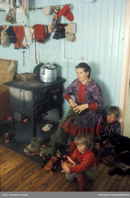 """Postfører Mathis Mathisen Buljo, bedre kjent som """"Post-Mathis"""" i samiske kretser, har stoppet innom en av sine postkunder på postruta. Samtalen går livlig fra kroken ved ovnen. Over vedoven henger votter og ulltøy til tørk.   Fotograf Henrik Ørsteds bilder er tatt langs den 30 mil lange postruta som strakk seg fra Mieronjavre poståpneri til Náhpolsáiva, videre til Bavtajohka, innover til øvre Anárjohka nasjonalpark som grenser til Finland – og ruta dekket nærmere 30 reindriftsenheter. Ørsted fulgte «Post-Mathis», Mathis Mathisen Buljo som dekket et imponerende område med omtrent 30.000 dyr og reingjetere som stadig var ute i terrenget og i forflytning. Dette var landets lengste postrute og postlevering under krevende vær- og føreforhold var beregnet til 2 dager. Bildene gir et unikt innblikk i samisk reindriftskultur på 1970-tallet. Fotograf Henrik Ørsted har donert ca. 1800 negativer og lysbilder til Finnmark Fylkesbibliotek i 2010."""