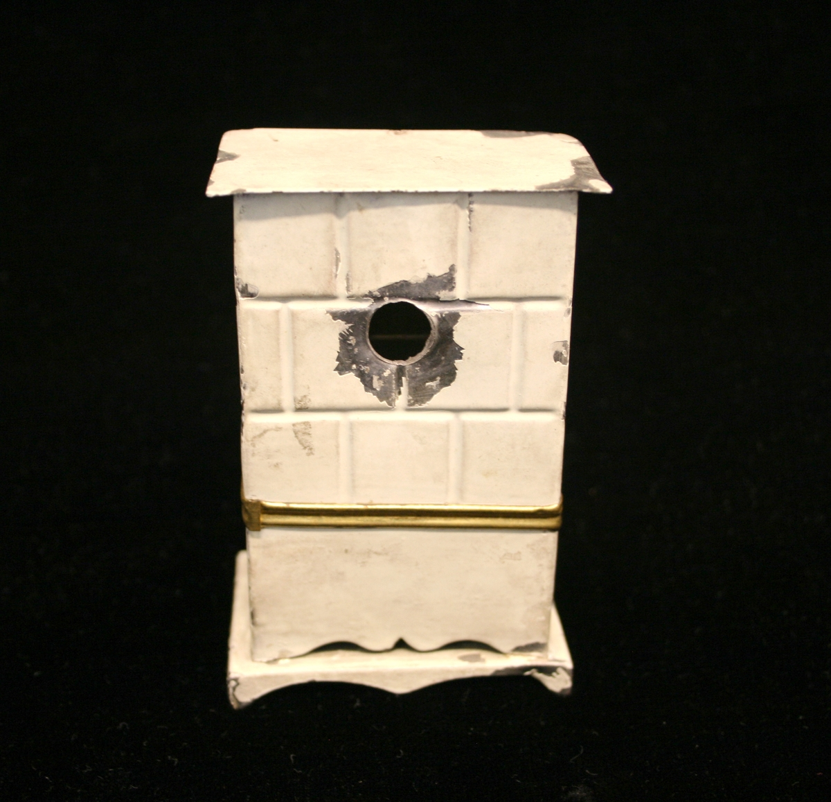 Ovn med messingskuff med dekor på. Gullkant som skiller nedre og øvre del, der øvre del har et støpt firkantet mønster, som hvit fajanseovn.