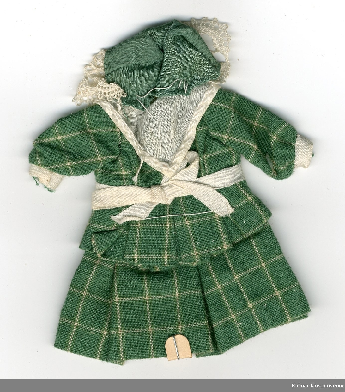 KLM 28082:14. Dockdräkt, dam, av textil, bomull och siden. Dräkten består av kjol, jacka, förkläde, schal och huvudbonad. Nationaldräkt från: Gotland.
