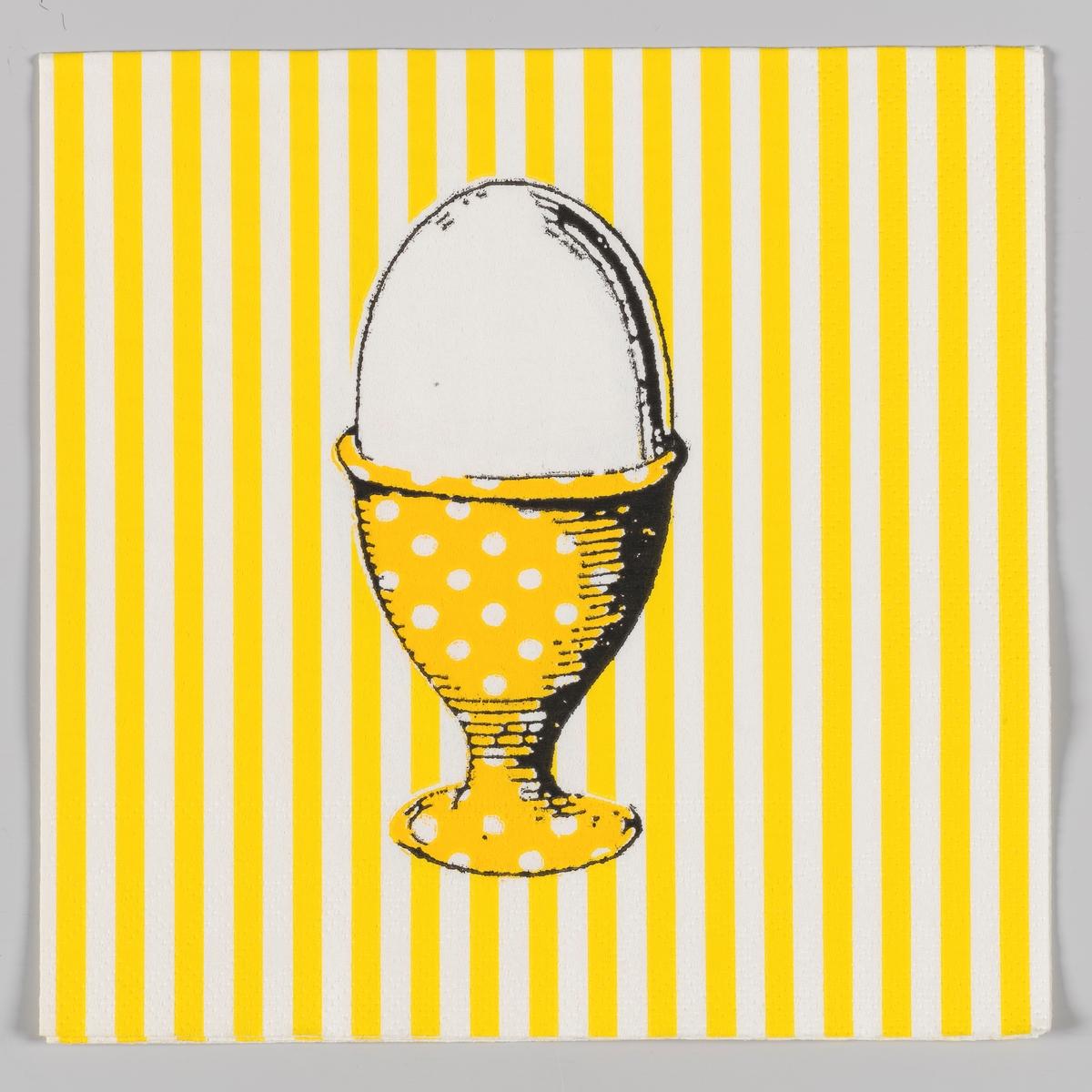 Et egg i et eggebeger utsmykket med hvite prikker på en gul og hvit stripet bakgrunn.
