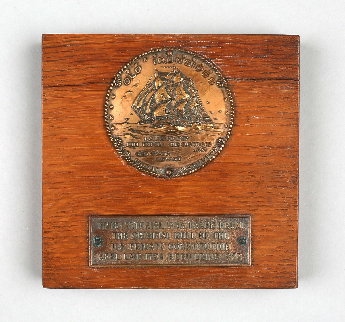Plakett i tre med minnemedalje med motiv av fregatten CONSTITUTIONEN som var sjøsatt i 1794/1797 og ombygd i 1927.