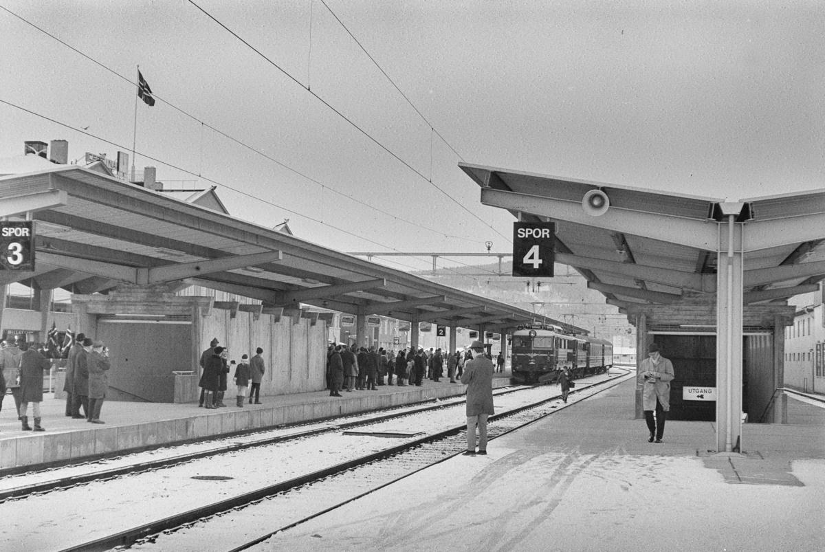 Mange fremmøtte på plattformen på Trondheim stasjon i forbindelse med åpningen av Dovrebanen for elektrisk drift. Åpningstoget kjører inn på stasjonen.