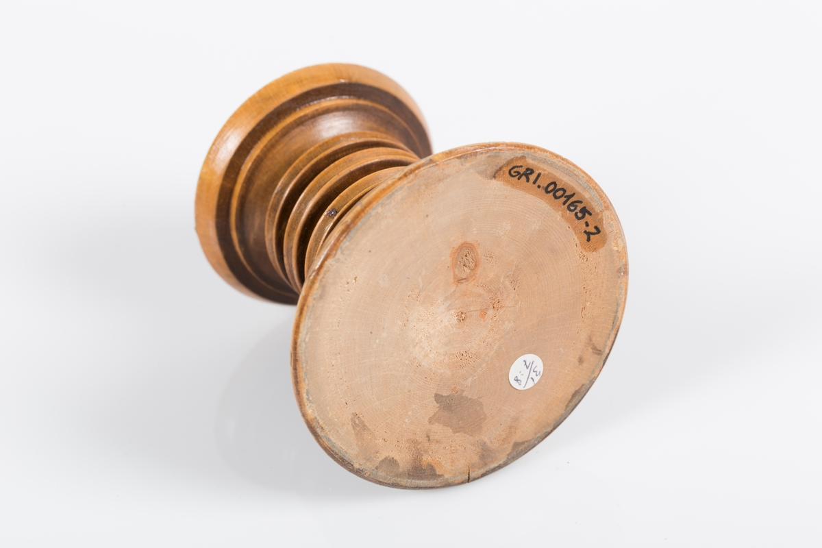 Lysestake i dreid tre. Lysestaken har rund form med en bredere rund fot. Rundt foten er det risset inn latinsk tekst (Jeg er verdens lys).