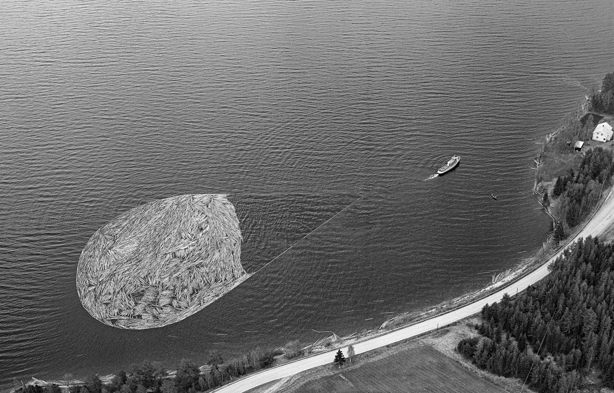 Flyfotografi, tatt over Fiskvikstøa i Ytre Rendalen, på Storsjøens vestside i 1981.  Vi ser hvordan riksveg 30 (her også kalt «Gamle kongeveg») slynget seg langs strandlinja. På vannspeilet ser vi en tømmerbom som ble slept sørover av tømmerslepebåten «Storsjø».  Det tok vanligvis drøyt 30 timer å trekke en slik ringbom fra området ved Åsheim i nordenden av innsjøen til utløpet i elva Søndre Rena, om lag 36 kilometer lengre sør.  Med de store tømmermengdene som ble fløtet i 1950- og 60-åra ble det gjerne omkring 30 turer, og sesongen varte om lag to måneder.  Da dette fotografiet ble tatt, i 1981, kunne 10-12 ringbommer romme det tømmeret som skulle fløtes ut av Rendalen.  Virksomheten ble avviklet etter 1984-sesongen.