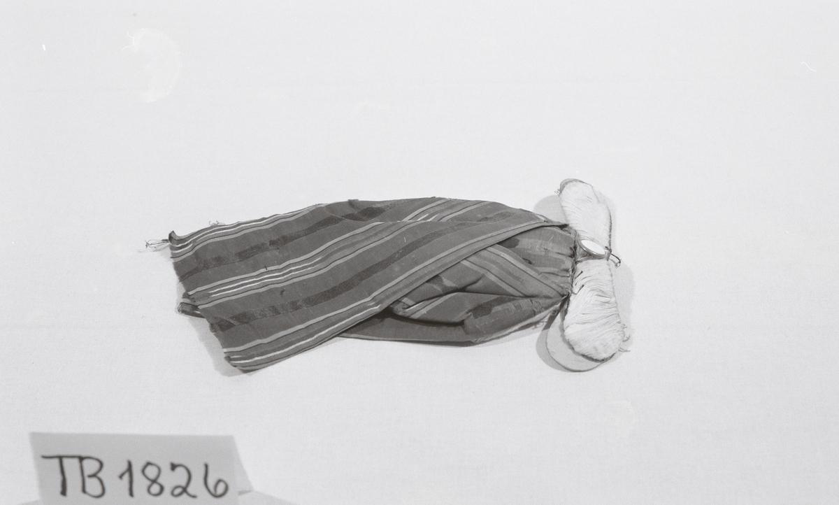 Hengende sløyfe i mønstrete stoff. Har vært festet til krage med knapp på stift. Stivet stykke i papp kledd med stoff til å stikke innunder snippene på kragen. Paddet bak. Slitt.