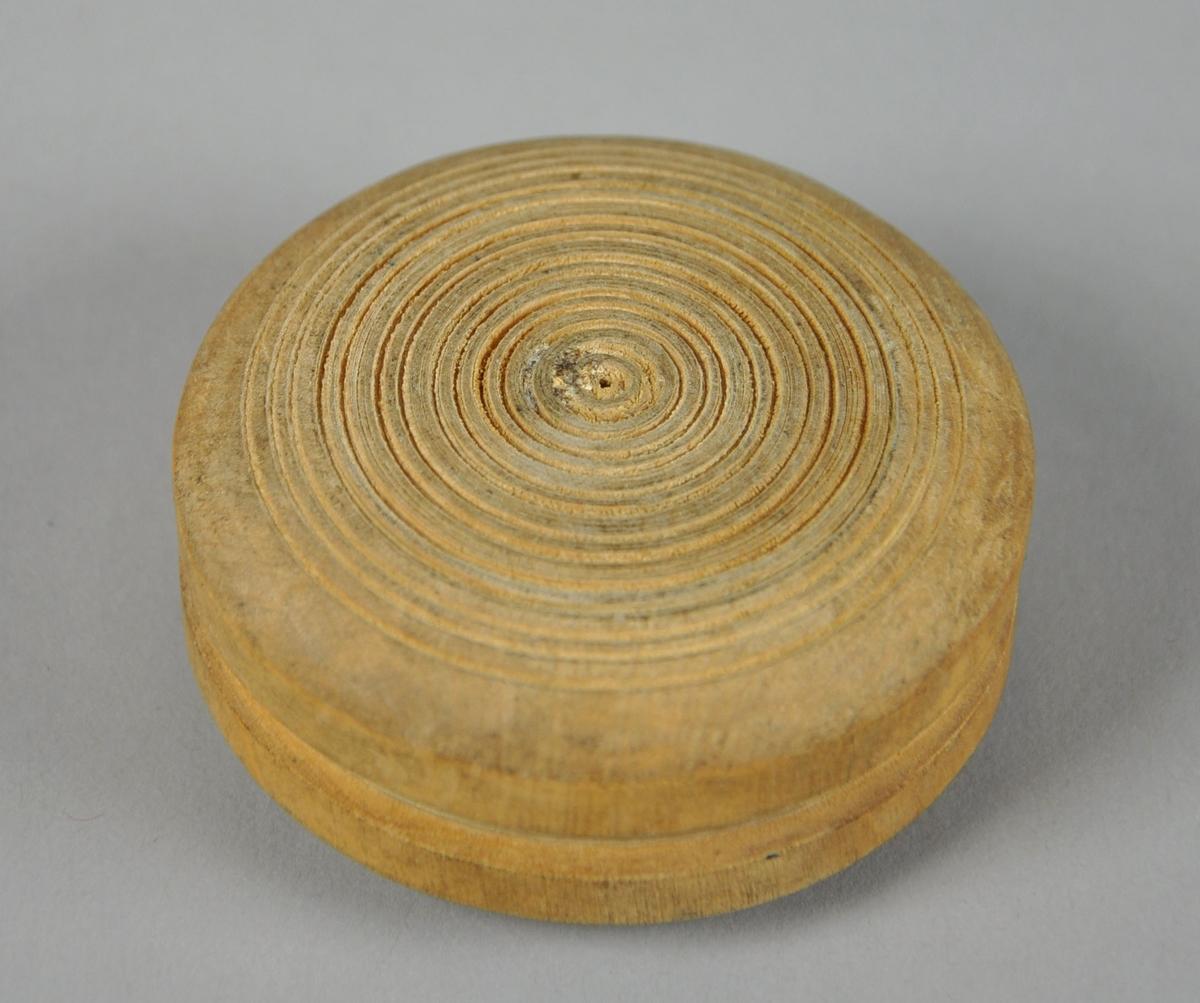 Rund eske av tre, med avtagbart lokk. Esken har innrisset dekor med sirkel- og kjettingmotiv, bunnen har konsentriske sirkler.