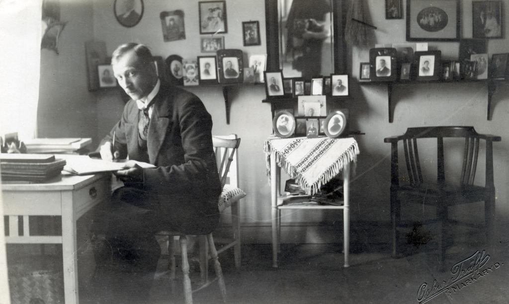 Oskar Träff sitter vid ett skrivbord placerat vid fönstret i ett rum. Längs väggen står ett flertal inramade porträttfotografier. I mitten hänger en spegel i vilken man kan se fotografen och kameran.