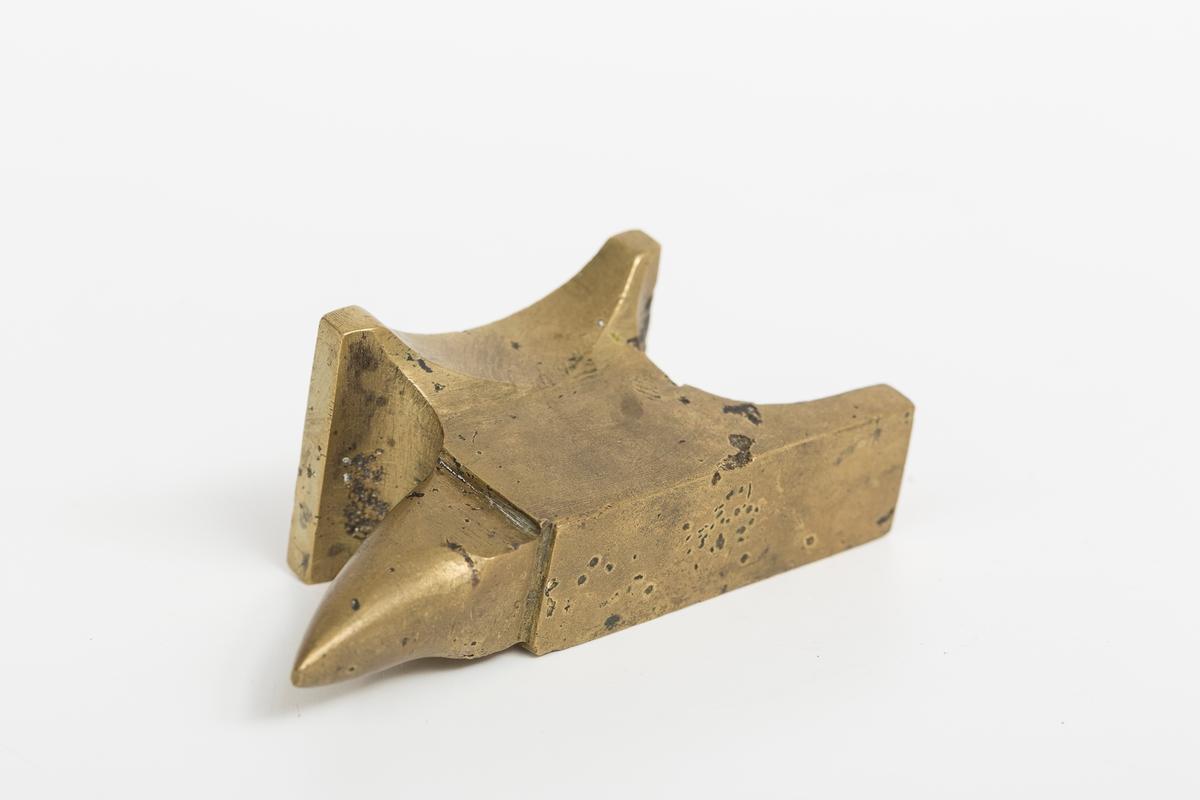 Messingambolt med tydelige bruksspor. Modell med hæl og horn. Mulig brukt av gullsmed eller finmekaniker.