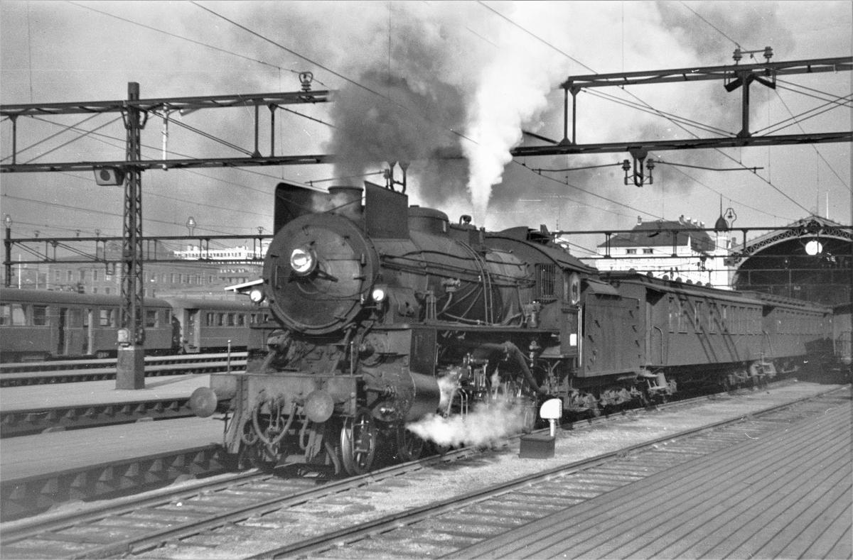 Persontog til Gjøvikbanen på Oslo Østbanestasjon. Toget trekkes av damplokomotiv type 31b nr. 451.
