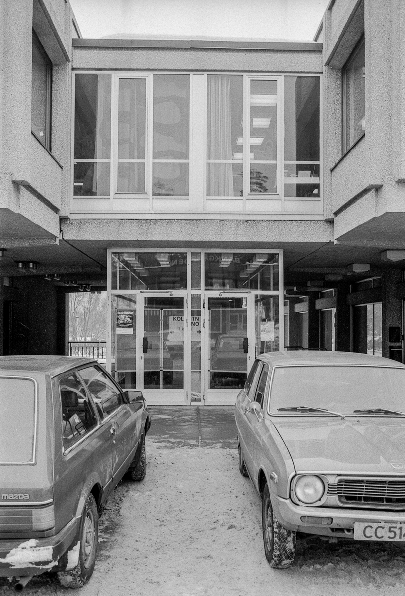 Sentrumsbygget på Kolbotn. Innganspartiet med parkerte biler foran. en mann går forbi. Rulletrappene nedenfra og ovenfra.