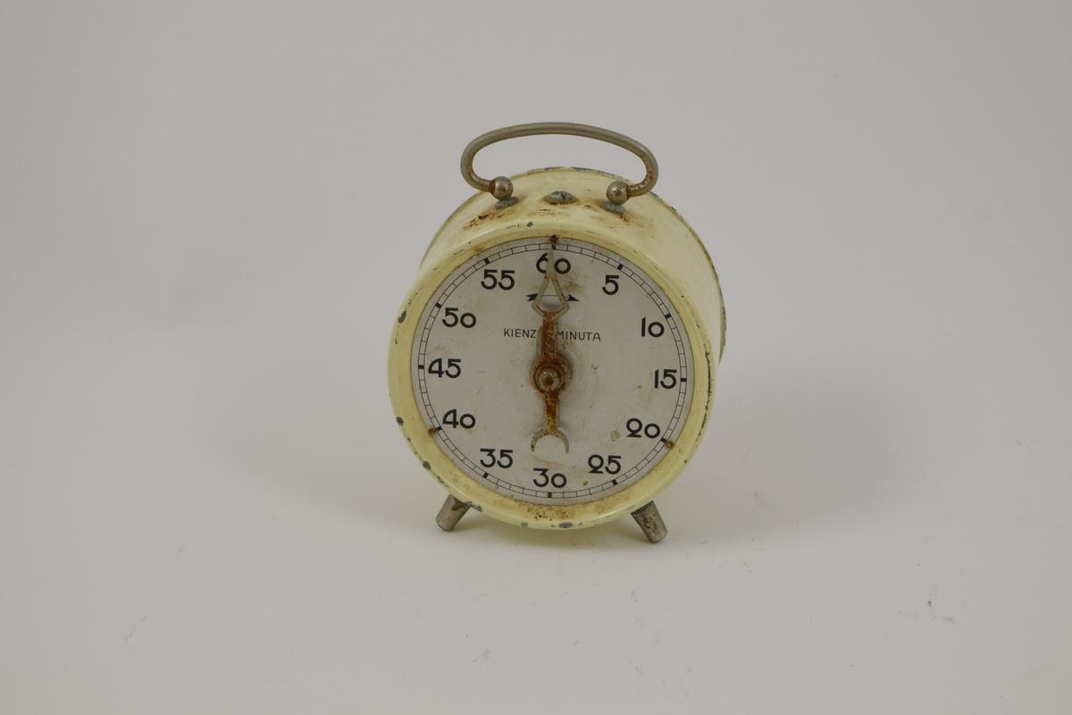 Rund klokke, to ben i forkant, håndtak på toppen. Hvit skive med sorte tall som vises i 5-minutters intervaller, fra 5 til 60. Viseren kan dreies for å stille alarmen.